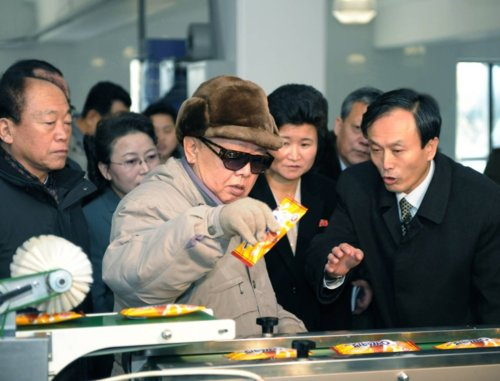 Kim Jong Il, with his entourage, looking at Chocolate